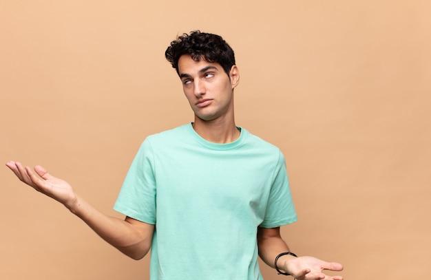 Junger gutaussehender mann, der mit einem dummen, verrückten, verwirrten, verwirrten ausdruck die achseln zuckt, sich verärgert und ahnungslos fühlt