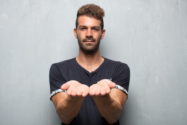 Junger gutaussehender mann, der mit einem erfüllten ausdruck zeigt einen gegenstand oder ein konzept lächelt
