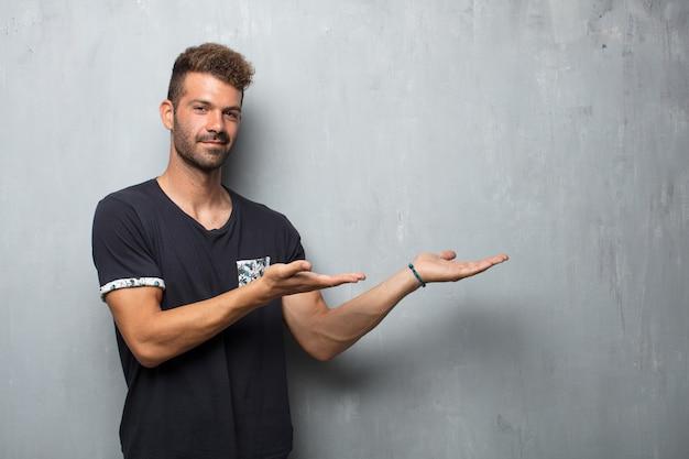 Junger gutaussehender mann, der mit einem erfüllten ausdruck zeigt einen gegenstand oder ein konzept mit beiden händen lächelt.