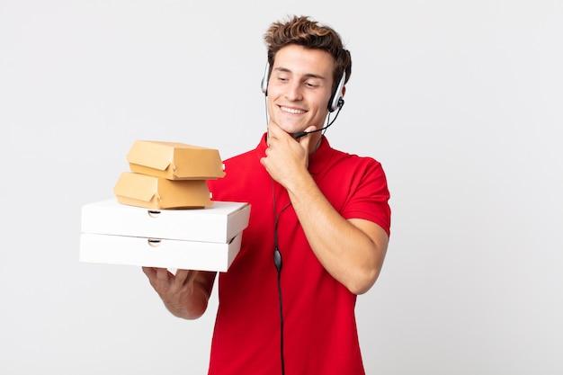 Junger gutaussehender mann, der mit einem glücklichen, selbstbewussten ausdruck mit der hand am kinn lächelt. take-away-fast-food-konzept