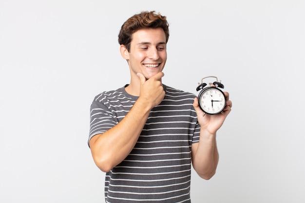 Junger gutaussehender mann, der mit einem glücklichen, selbstbewussten ausdruck mit der hand am kinn lächelt und einen wecker hält