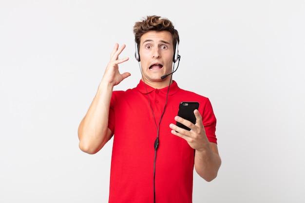 Junger gutaussehender mann, der mit einem smartphone und einem headset mit den händen in die luft schreit