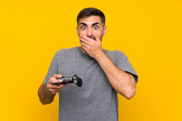 Junger gutaussehender mann, der mit einem videospielcontroller über lokalisiertem gelbem hintergrund mit überraschungsgesichtsausdruck spielt