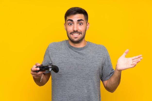 Junger gutaussehender mann, der mit einem videospielcontroller über lokalisierter gelber wand mit entsetztem gesichtsausdruck spielt