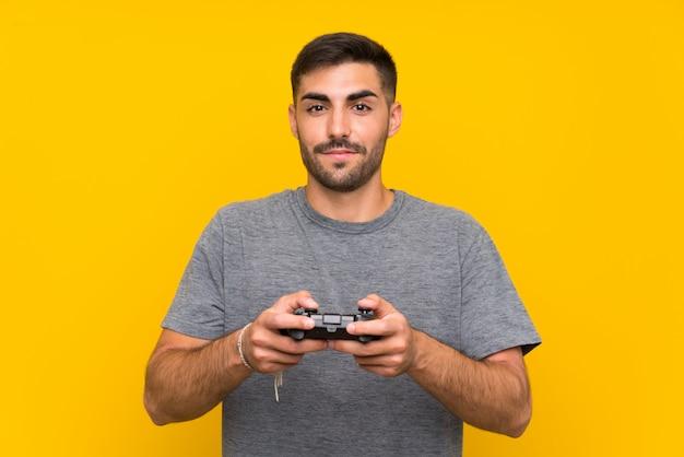 Junger gutaussehender mann, der mit einem videospielcontroller über lokalisierter gelber wand spielt