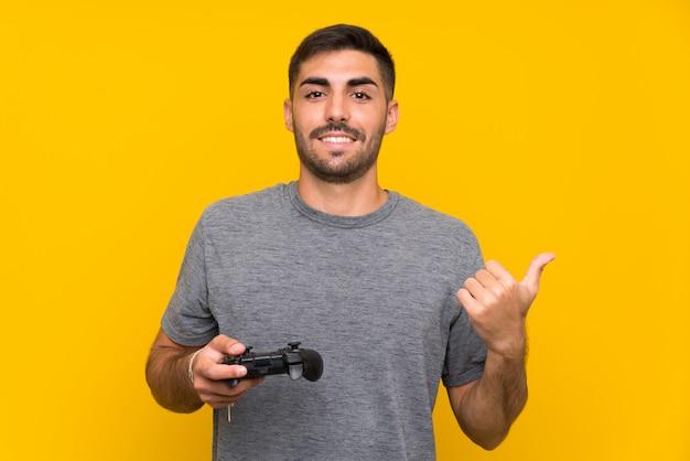 Junger gutaussehender mann, der mit einem videospielcontroller über lokalisierter gelber wand zeigt auf die seite spielt, um ein produkt darzustellen