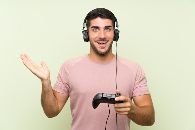 Junger gutaussehender mann, der mit einem videospielcontroller über lokalisierter grüner wand mit entsetztem gesichtsausdruck spielt