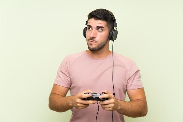 Junger gutaussehender mann, der mit einem videospielcontroller über lokalisierter grüner wand spielt