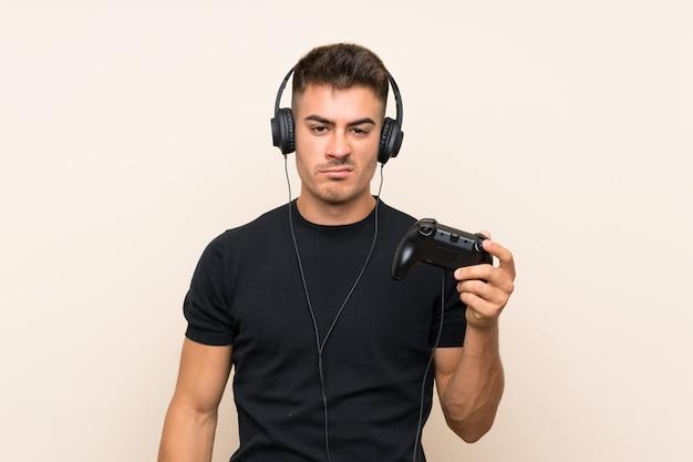 Junger gutaussehender mann, der mit einem videospielcontroller über lokalisierter wand mit traurigem ausdruck spielt