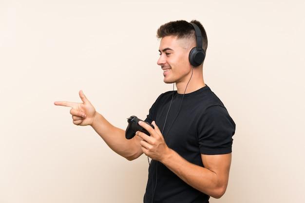 Junger gutaussehender mann, der mit einem videospielcontroller über lokalisierter wand zeigt auf die seite spielt, um ein produkt darzustellen