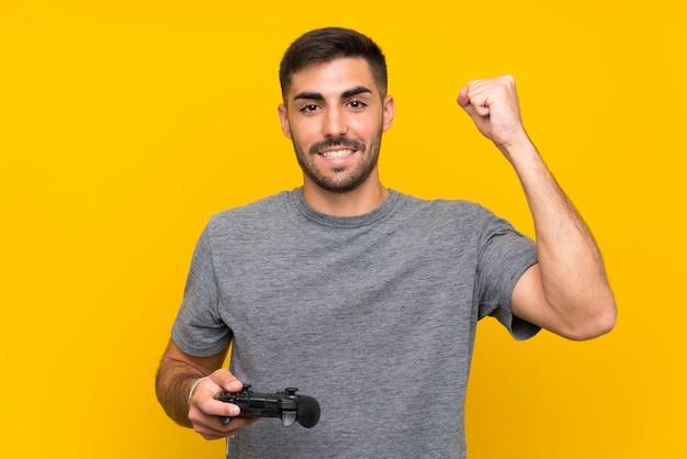 Junger gutaussehender mann, der mit einem videospielprüfer über der lokalisierten gelben wand feiert einen sieg spielt