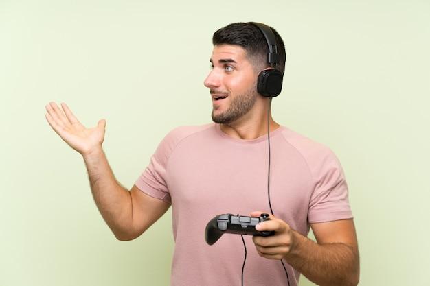 Junger gutaussehender mann, der mit einem videospielprüfer über lokalisierter grüner wand mit überraschungsgesichtsausdruck spielt