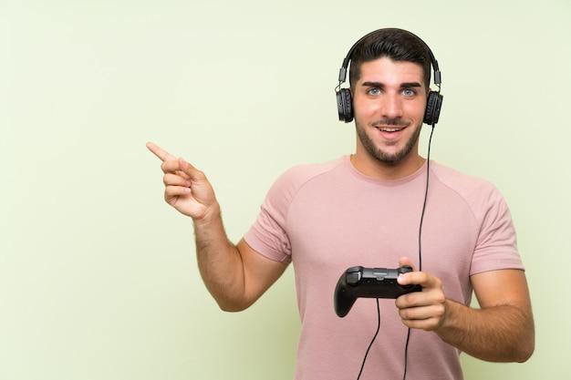 Junger gutaussehender mann, der mit einem videospielprüfer über lokalisierter grüner wand überrascht spielt und finger auf die seite zeigt