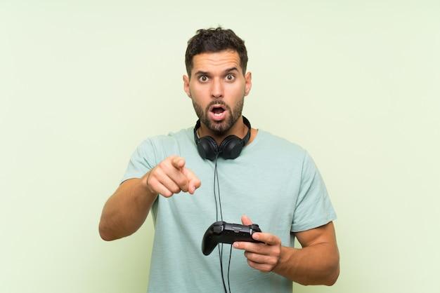 Junger gutaussehender mann, der mit einem videospielprüfer über lokalisierter grüner wand überrascht spielt und front zeigt