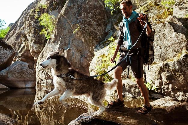 Junger gutaussehender mann, der mit huskys hund in der schlucht nahe wasser geht