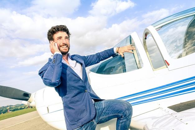 Junger gutaussehender mann, der mit intelligentem mobiltelefon am privaten flugzeug spricht
