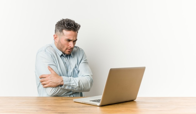 Junger gutaussehender mann, der mit seinem laptop geht kalt wegen der niedrigen temperatur oder einer krankheit arbeitet.