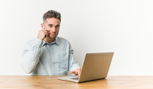 Junger gutaussehender mann, der mit seinem laptop mit den fingern auf den lippen hält ein geheimnis arbeitet.