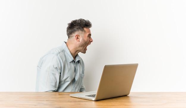 Junger gutaussehender mann, der mit seinem laptop schreit in richtung zu einem kopienraum arbeitet