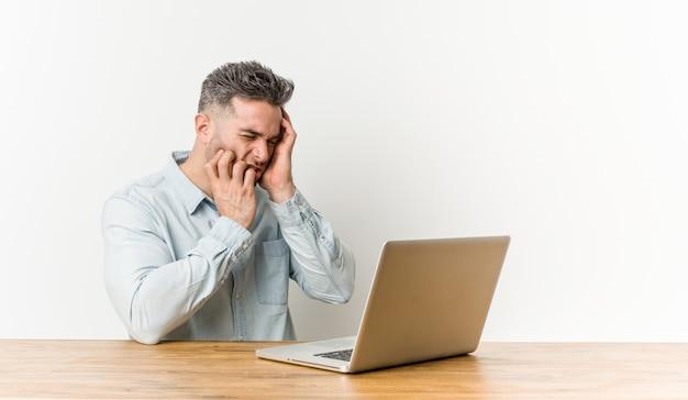 Junger gutaussehender mann, der mit seinem laptop trostlos jammern und schreien arbeitet