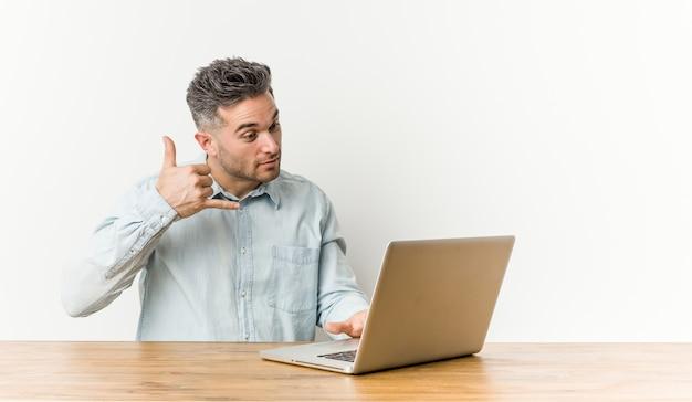 Junger gutaussehender mann, der mit seinem laptop zeigt eine handyanrufgeste mit den fingern arbeitet.