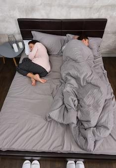 Junger gutaussehender mann, der mit seiner freundin schläft, nur er selbst vollständig in eine decke gehüllt, im pyjama, in der nähe des nachttisches mit kerzen