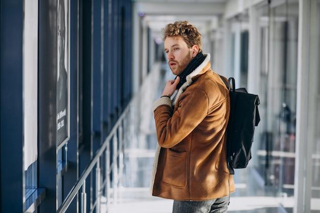 Junger gutaussehender mann, der mit tasche reist