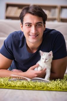 Junger gutaussehender mann, der mit weißem kätzchen spielt