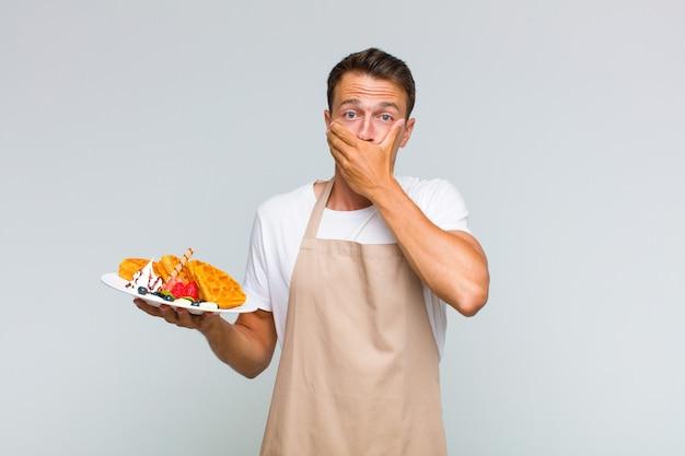 Junger gutaussehender mann, der mund mit händen mit einem schockierten, überraschten ausdruck bedeckt, ein geheimnis hält oder oops sagt