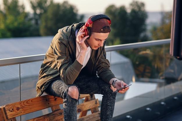 Junger gutaussehender mann, der musik in den kopfhörern und im telefon auf dem dach des industriegebäudes am sonnenuntergang hört.