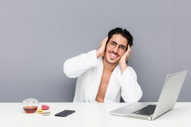 Junger gutaussehender mann, der nach einer dusche arbeitet, lacht freudig und hält hände auf kopf. glückskonzept.
