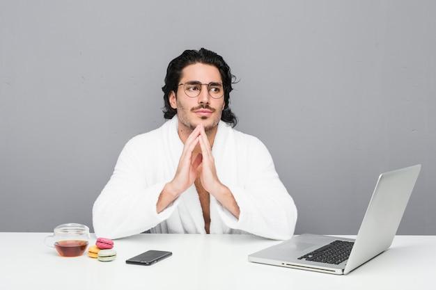 Junger gutaussehender mann, der nach einer dusche arbeitet plan im sinn, eine idee aufstellend