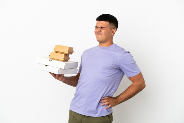 Junger gutaussehender mann, der pizza und burger über isoliertem weißem hintergrund hält und an rückenschmerzen leidet, weil er sich bemüht hat