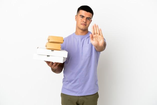 Junger gutaussehender mann, der pizza und burger über isoliertem weißem hintergrund hält und stopp-geste macht