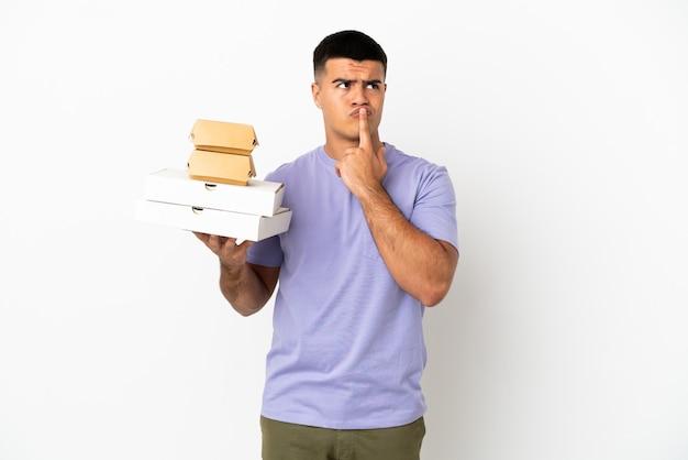 Junger gutaussehender mann, der pizza und burger über isoliertem weißem hintergrund hält und zweifel hat, während er nach oben schaut
