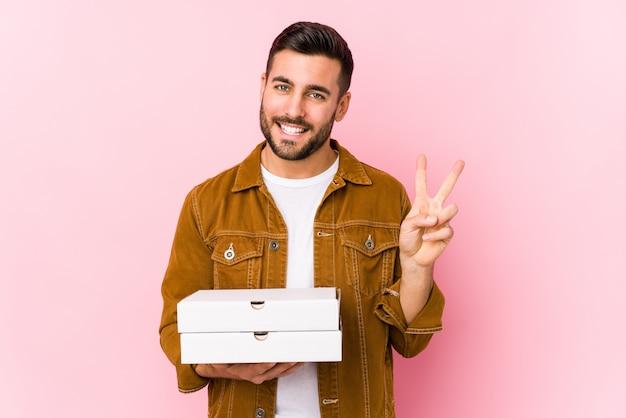 Junger gutaussehender mann, der pizzas lokalisiert hält, nummer zwei mit den fingern zeigend.