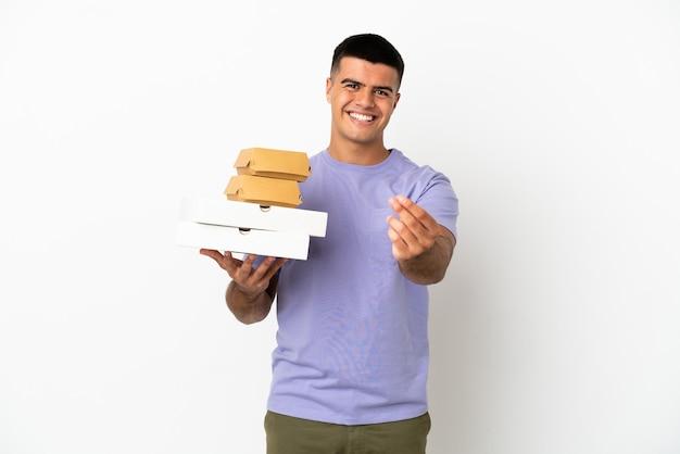 Junger gutaussehender mann, der pizzas und burger über isoliertem weißem hintergrund hält und geldgeste macht