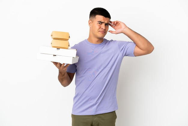 Junger gutaussehender mann, der pizzen und burger über isoliertem weißem hintergrund hält und zweifel hat