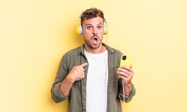 Junger gutaussehender mann, der schockiert und überrascht mit weit geöffnetem mund aussieht und auf selbstkopfhörer und smartphone-konzept zeigt