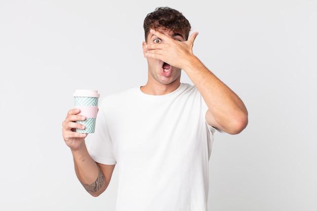Junger gutaussehender mann, der schockiert, verängstigt oder verängstigt aussieht, das gesicht mit der hand bedeckt und einen kaffee zum mitnehmen hält