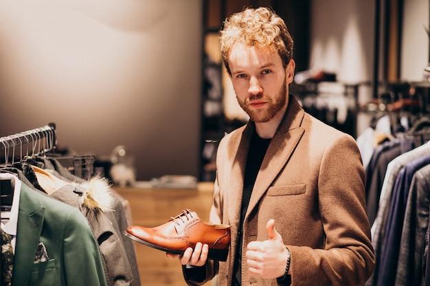 Junger gutaussehender mann, der schuhe an einem shop wählt