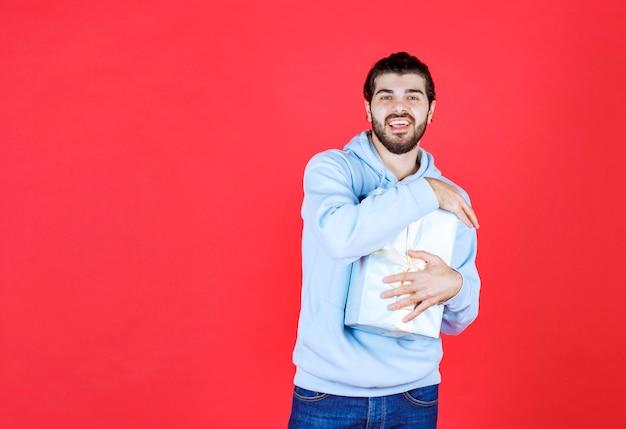 Junger gutaussehender mann, der seine verpackte geschenkbox umarmt