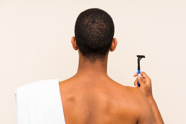 Junger gutaussehender mann, der seinen bart über lokalisierter wand in hinterer position rasiert