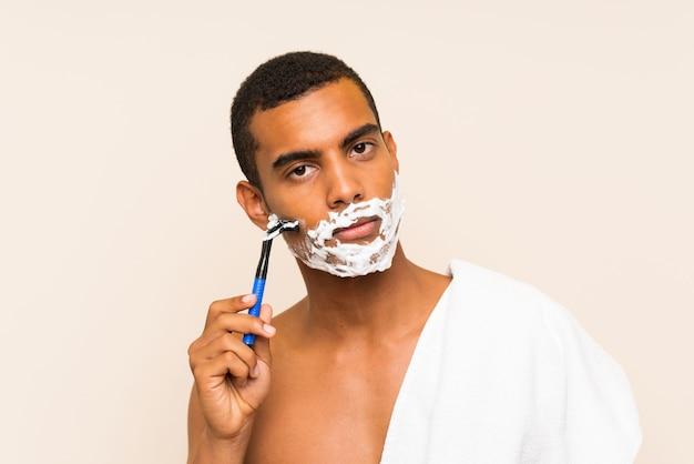 Junger gutaussehender mann, der seinen bart über lokalisierter wand rasiert