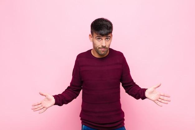 Junger gutaussehender mann, der sich ahnungslos und verwirrt fühlt, keine ahnung hat, absolut verwirrt mit einem dummen oder dummen blick gegen rosa wand
