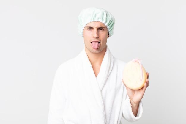 Junger gutaussehender mann, der sich angewidert und gereizt fühlt und die zunge mit bademantel, duschhaube und einem schwamm herausstreckt
