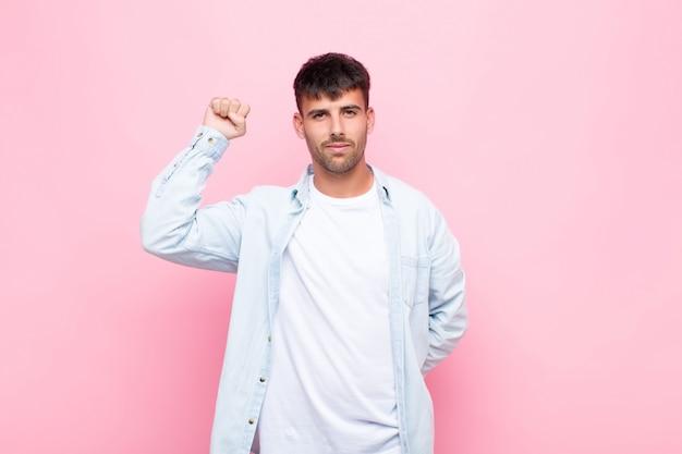 Junger gutaussehender mann, der sich ernst, stark und rebellisch fühlt, die faust erhebt, protestiert oder für die revolution gegen die rosa wand kämpft