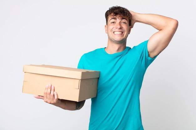 Junger gutaussehender mann, der sich gestresst, ängstlich oder verängstigt fühlt, die hände auf dem kopf hat und einen karton hält