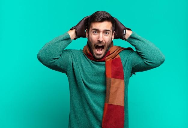 Junger gutaussehender mann, der sich gestresst, besorgt, ängstlich oder ängstlich fühlt, mit händen auf dem kopf, die bei einem fehler in panik geraten. kalt und winter concetp