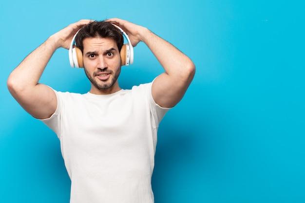 Junger gutaussehender mann, der sich gestresst, besorgt, ängstlich oder ängstlich fühlt, mit händen auf dem kopf, die bei einem fehler in panik geraten